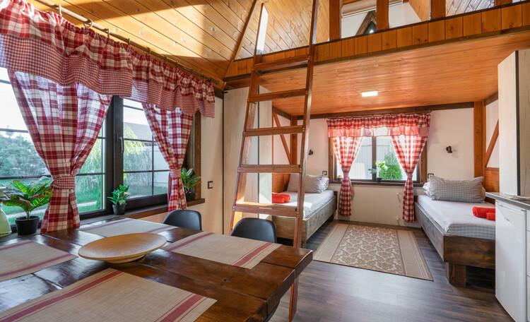 Домик-студия: Первый этаж - 2 кровати, кухонная зона, санузел. На мансардном этаже двуспальная кровать.