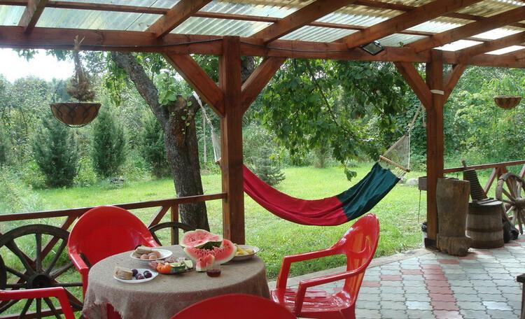 Усадьба «Олизаров став». Крытая терраса у развесистой яблони. Террасу украшают предметы старины и дизайнерского искусства.