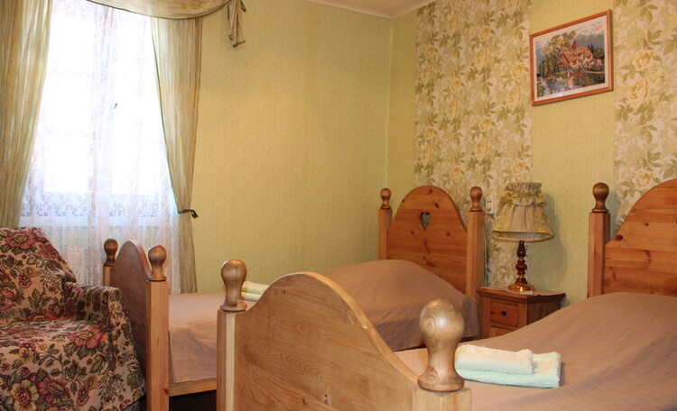 Усадьба «Олизаров став». Спальня c двумя полутороспальными кроватями из массива дерева.