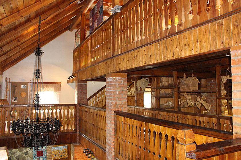 Музей традиционной культуры в Браславе, Второй этаж музея. Бросается в глаза большое количество дерева, кованый светильник, и много золотистых соломенных зверюшек